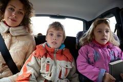 De moeder met kinderen zit op achterbank van auto Stock Foto's