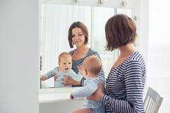 De moeder met 8 maanden oud baby kijkt thuis in een spiegel royalty-vrije stock foto