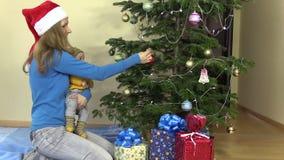 De moeder met pasgeboren baby in haar handen hangt Kerstboomstuk speelgoed stock videobeelden