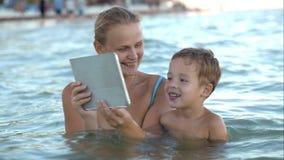 De moeder met stootkussen toont binnen zijn zoonsfoto of video stock footage