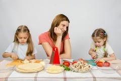 De moeder met tederheid kijkt als haar weinig dochter om haar in keuken te helpen om maaltijd voor te bereiden Stock Fotografie