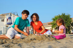 De moeder met vader en het meisje zitten op strand royalty-vrije stock foto