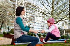 De moeder met weinig dochter speelt bij carrousel royalty-vrije stock fotografie