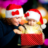 De moeder met weinig kind opent de doos met giften op Kerstmis Royalty-vrije Stock Foto's