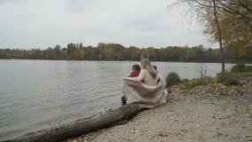 De moeder met zonen zit op een logboek dichtbij de rivier en de familie geniet de herfst van mening stock footage