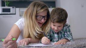 De moeder met zoon trekt met gekleurde tellers op wit blad binnen liggend op vloer bij weekend stock video