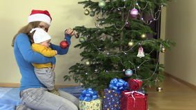 De moeder met zuigelingsbaby in haar handen hangt Kerstboomstuk speelgoed stock videobeelden