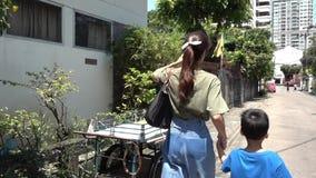De moeder neemt haar zoon voor een gang in stille straat van Bangkok stock video