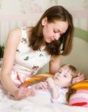 De moeder omhelst het zieke kind stock afbeelding