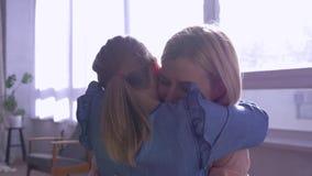 De moeder omhelst, stort weinig dochter zich in mammawapens overhaast en geeft thuis grote omhelzing tegen venster in zonstralen