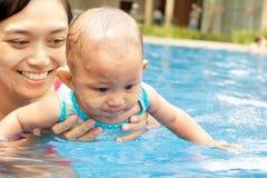 De moeder onderwijst baby om te zwemmen Stock Afbeeldingen