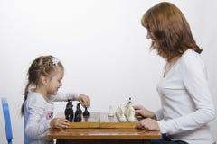 De moeder onderwijst dochter om schaak te spelen Stock Afbeeldingen