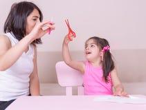 De moeder onderwijst haar dochter hoe te om schaar te gebruiken royalty-vrije stock foto