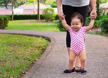 De moeder onderwijst haar gelukkige jonge dochter hoe te om op haar te lopen Stock Foto