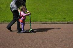 De moeder onderwijst haar kind om een autoped te berijden Royalty-vrije Stock Foto