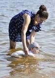 De moeder onderwijst het jonge geitje om voor het eerst te zwemmen Royalty-vrije Stock Foto