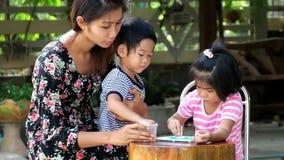 De moeder onderwijst het spel van het jong geitjespel vreugdevol, het spel van het familiespel samen stock video