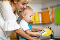 De moeder onderwijst was-omhoog haar weinig kindzoon aan stock fotografie