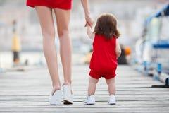 De moeder onderwijst weinig dochter om alleen te lopen stock foto