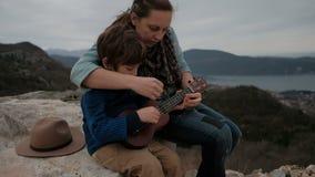 De moeder onderwijst zoon om gitaarzitting op de kust op een steen samen te spelen stock videobeelden