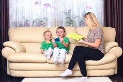 De moeder is ongelukkig dat de kinderen met de telefoon spelen stock foto