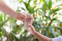 De moeder overhandigde het glas aan het kind royalty-vrije stock afbeeldingen