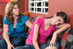 De moeder probeert om haar droevige tienerdochter te troosten Stock Afbeelding