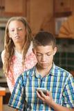 De moeder probeert te gluren aangezien de tienerzoon zijn mobiele telefoon controleert Stock Foto's
