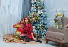 De moeder in rode kleding glimlacht en houdt een mooie baby Royalty-vrije Stock Afbeeldingen