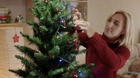 De moeder in rode trui die nieuwe jaarboom decotating met wonned stuk speelgoed rode ster stock videobeelden