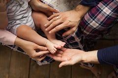 De moeder ` s en de vader` s handen houden de kleine benen van hun stock afbeelding