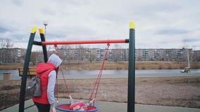 De moeder schudt haar kind op schommeling in park op bewolkte dag stock footage