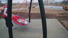 De moeder schudt haar kind op schommeling in park op bewolkte dag stock video