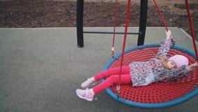De moeder schudt haar kind op schommeling in park op bewolkte dag stock videobeelden