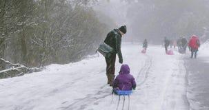 De moeder sleept een kleine jongen onderaan een sneeuwweg op toboggan stock footage