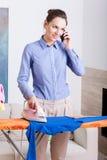 De moeder spreekt op telefoon terwijl het strijken Royalty-vrije Stock Afbeelding