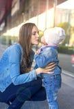 De moeder staat enkel haar dochter` s kus te zetten op het punt stock afbeelding