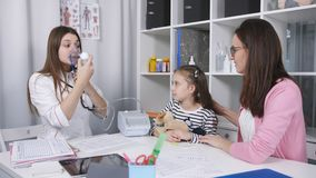 De moeder steunt en kalmeert weinig dochter in de spreekkamer tot haar dochter ingaliruut door een masker te gebruiken stock videobeelden