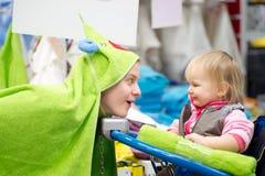 De moeder toont aan baby in boodschappenwagentje groene handdoek Royalty-vrije Stock Afbeelding