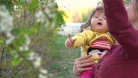 De moeder toont aan babybloemen op bomen in slowmo stock videobeelden