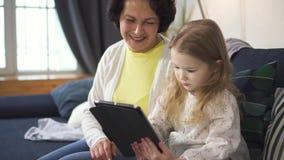 De moeder toont charmante meisjelaptop en het controlescherm van tablet stock footage