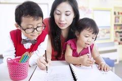 De moeder toont kinderen hoe te te schrijven Royalty-vrije Stock Foto