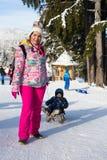 De moeder trekt een slee met haar zoon Royalty-vrije Stock Foto's