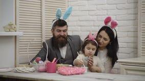 De moeder, de vader en de dochter schilderen paaseieren De gelukkige familie treft voor Pasen voorbereidingen Leuk weinig kindmei stock video