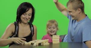 De moeder, de vader en de dochter spelen jenga Het maken van een toren van houten blokken stock video