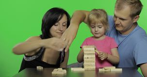 De moeder, de vader en de dochter spelen jenga Het maken van een toren van houten blokken stock footage