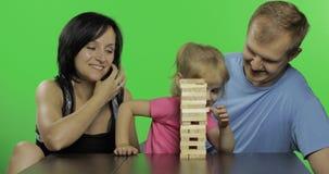 De moeder, de vader en de dochter spelen jenga Trekt houten blokken van toren stock videobeelden