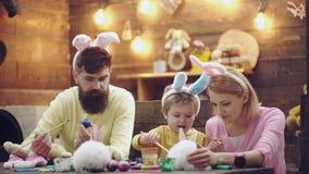 De moeder, de vader en de zoon schilderen eieren De gelukkige familie treft voor Pasen voorbereidingen Leuk weinig kindjongen die stock video
