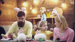 De moeder, de vader en de zoon schilderen paaseieren De gelukkige familie treft voor Pasen voorbereidingen Leuk weinig kindjongen stock footage