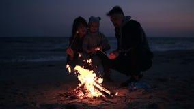 De moeder, vader in warme kleren roostert heemst op houten stokken met hun kleine baby Vuur op het strand stock videobeelden